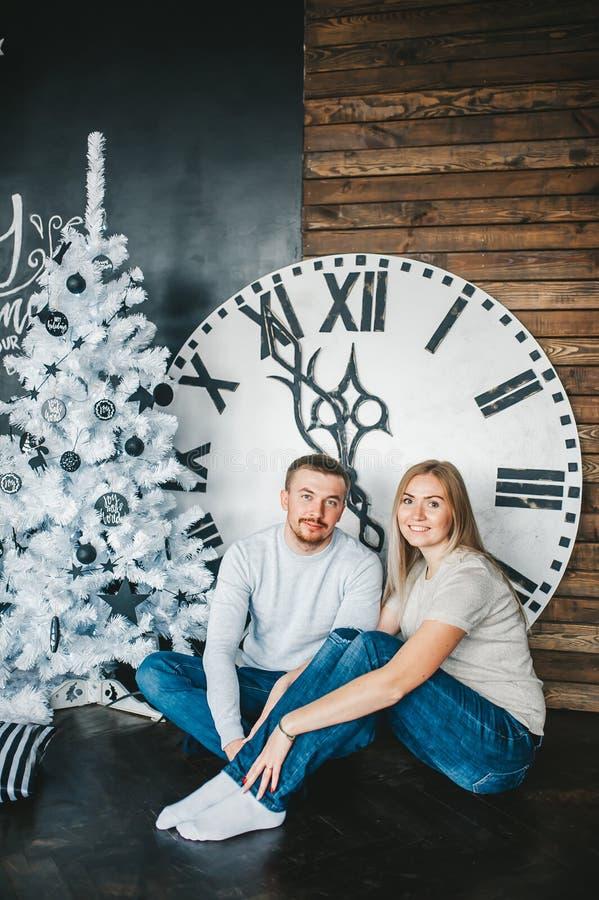 Молодая пара сидит на поле около ели рождества в комнате на фоне больших настенных часов стоковое изображение rf