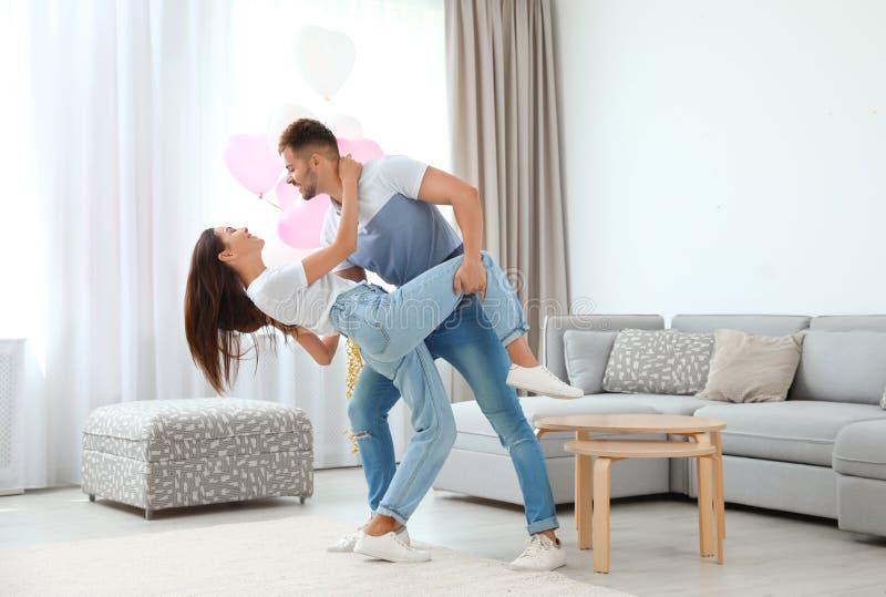 Молодая пара танцует в гостиной, украшенная шарлатами Празднование Дня Святого Валентина стоковые фото