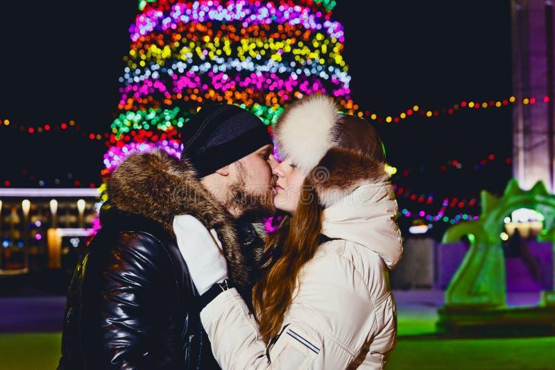 Молодая пара целует между рождественскими елками outdoors стоковая фотография