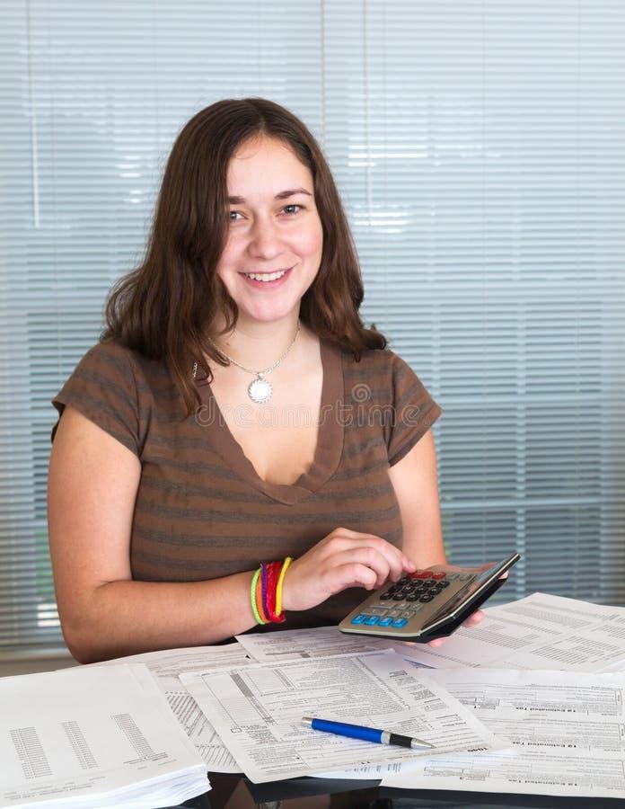 Молодая повелительница подготовляя налоговую форму 1040 США на 2012 стоковая фотография
