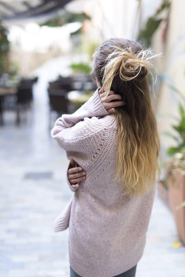 Молодая подростковая женщина от заднего касающся ее волосам стоковые фотографии rf