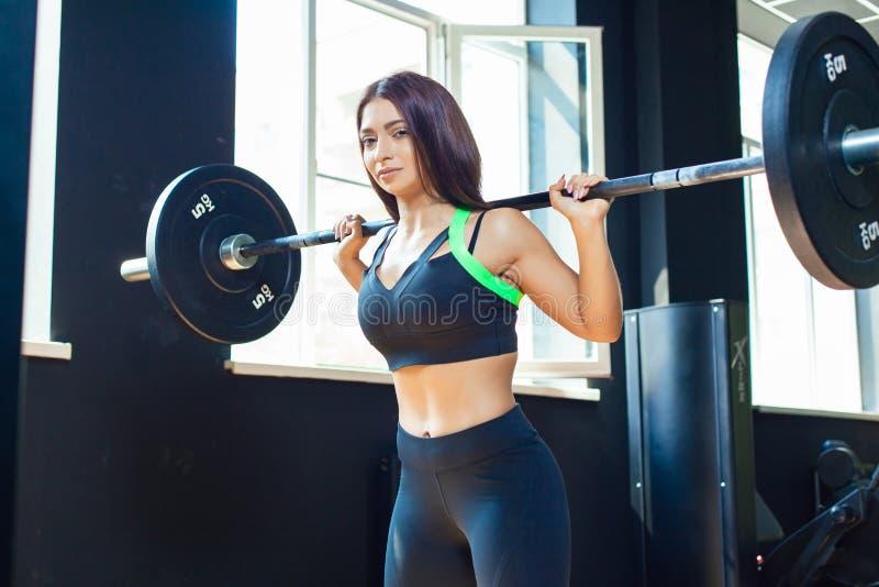 Молодая подходящая девушка делая сверхмощные сидения на корточках в спортзале со штангой в красивом sportswear стоковые фотографии rf