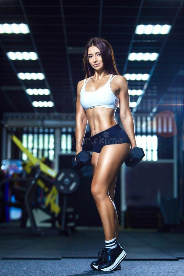 Молодая подходящая женщина в sporty шортах и верхних держа гантелях пока стоящ в спортзале стоковое фото rf