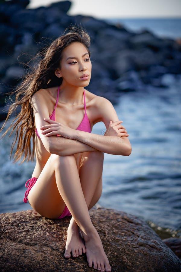 Молодая постная милая азиатская девушка в 2 частях розового купальника ослабить на seashore стоковые фото