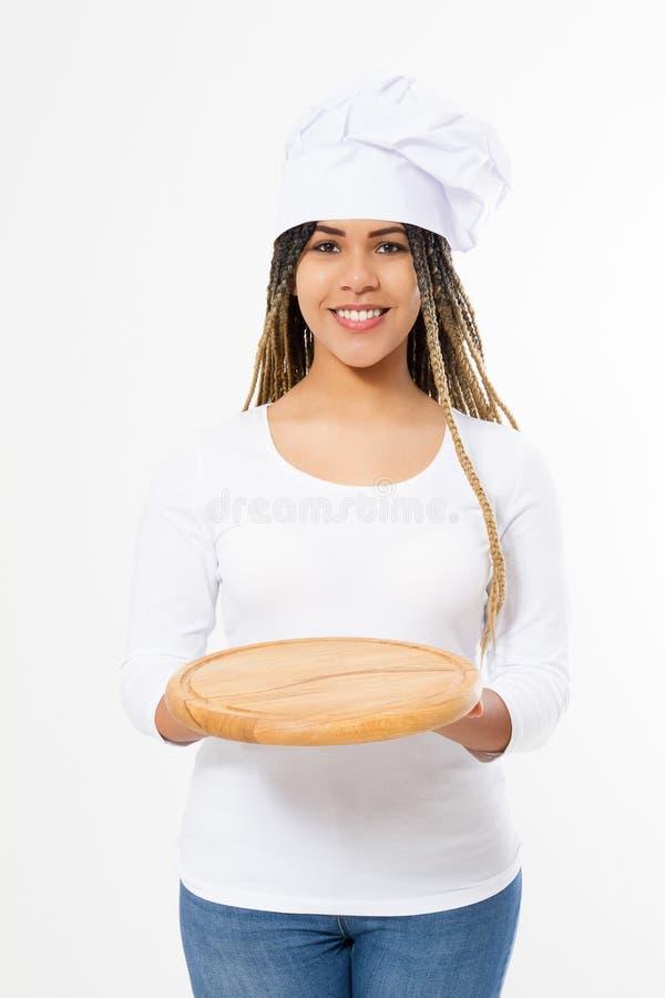 Молодая привлекательная Афро-американская женщина в варить шляпу держа пустую деревянную разделочную доску пиццы изолированный на стоковое фото