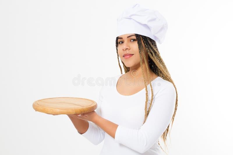 Молодая привлекательная Афро-американская женщина в варить шляпу держа пустую деревянную разделочную доску пиццы изолированный на стоковая фотография rf