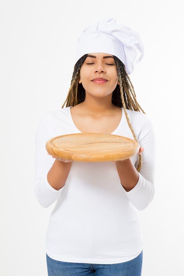 Молодая привлекательная Афро-американская женщина в варить шляпу держа пустую деревянную разделочную доску пиццы изолированный на стоковое фото rf