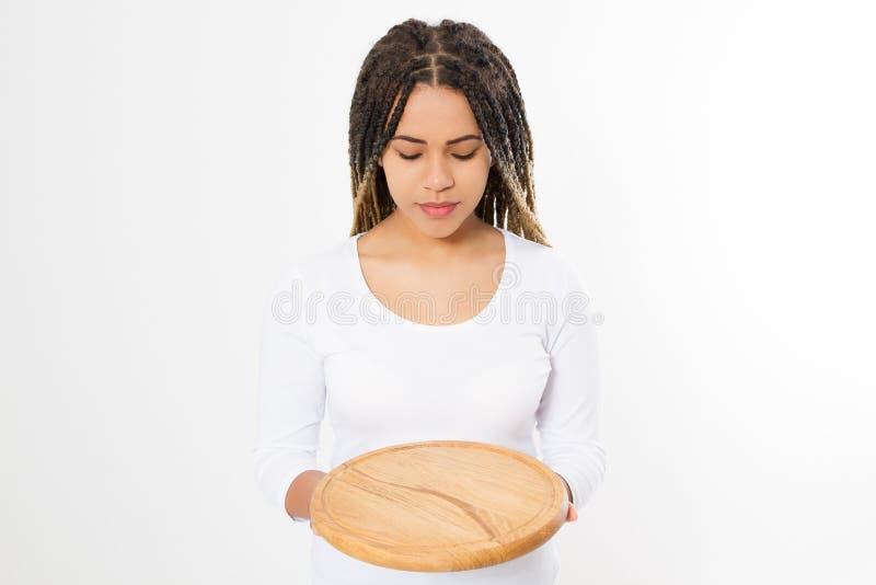 Молодая привлекательная Афро-американская женщина держа пустую деревянную разделочную доску пиццы изолированный на белой предпосы стоковое изображение
