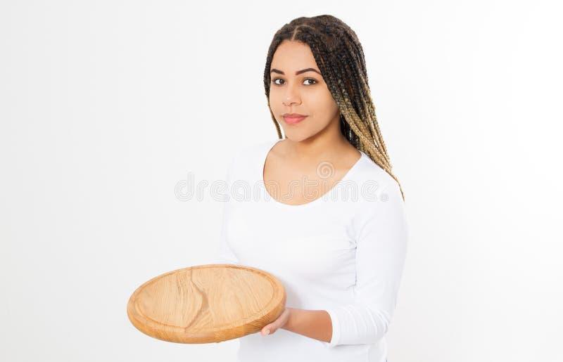 Молодая привлекательная Афро-американская женщина держа пустую деревянную разделочную доску пиццы изолированный на белой предпосы стоковая фотография rf