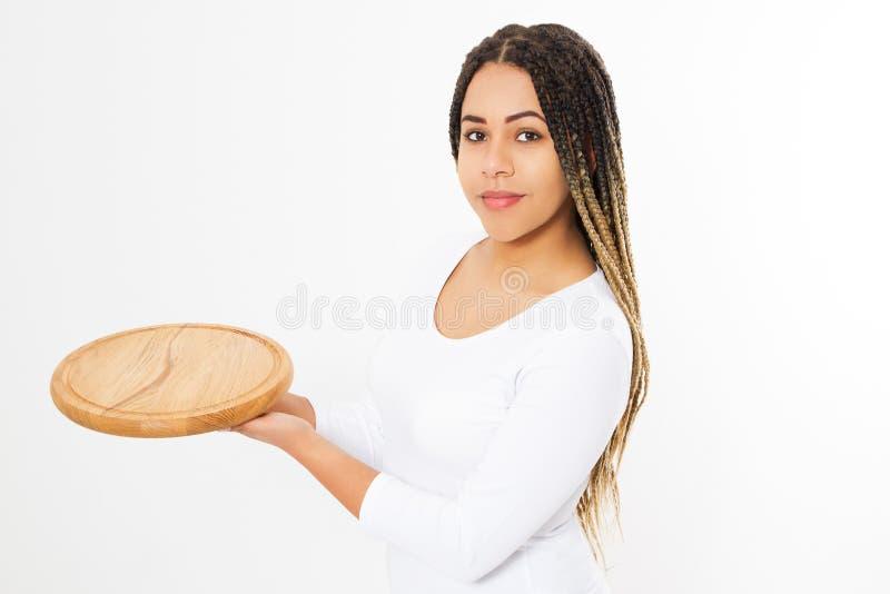 Молодая привлекательная Афро-американская женщина держа пустую деревянную разделочную доску пиццы изолированный на белой предпосы стоковые изображения rf