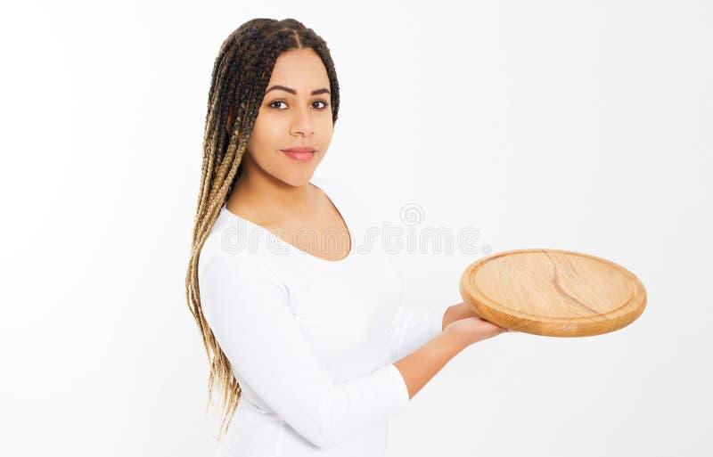 Молодая привлекательная Афро-американская женщина держа пустую деревянную разделочную доску пиццы изолированный на белой предпосы стоковое фото