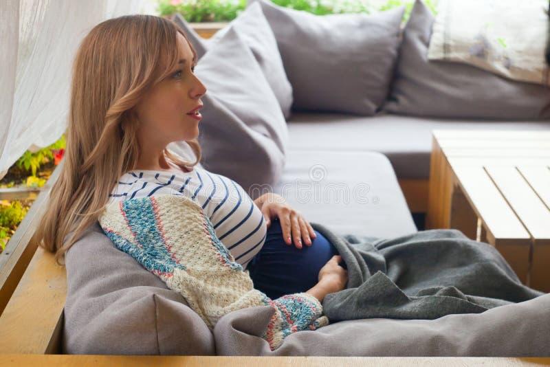 Молодая привлекательная беременная женщина охлаждая на кафе террасы стоковая фотография