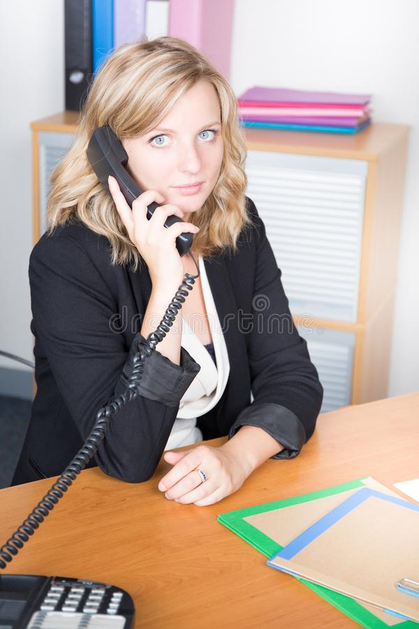 Молодая привлекательная бизнес-леди используя телефон на офисе стоковое изображение rf