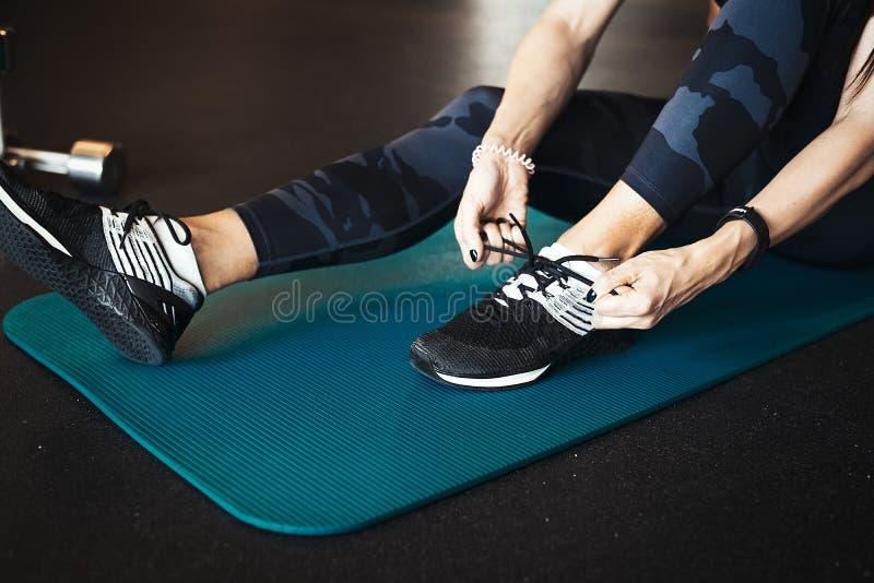 Молодая привлекательная девушка брюнет enlacing ее ботинки спорта после практиковать тренировку разминки и crossfit на голубой ци стоковые фотографии rf