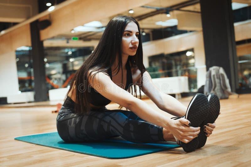Молодая привлекательная девушка брюнет enlacing ее ботинки спорта после практиковать тренировку разминки и crossfit на голубой ци стоковая фотография rf