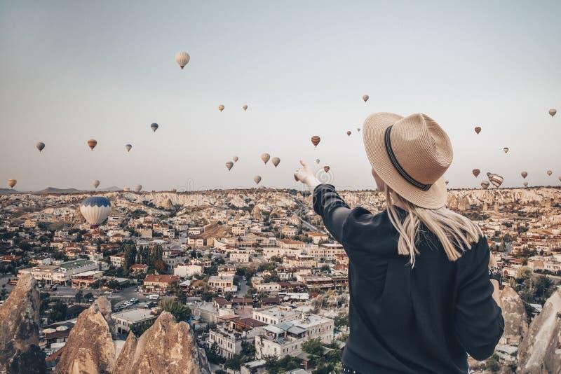 Молодая привлекательная девушка в шляпе стоит на горе с летящими воздушными шариками на заднем плане Девушка, указывающая пальцем стоковые фото
