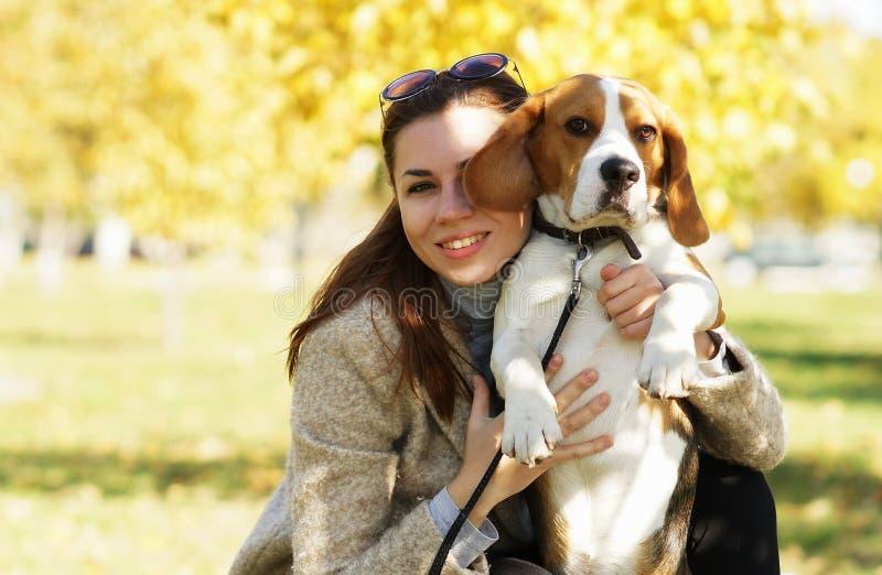 Молодая привлекательная девушка обнимая ее милую собаку бигля стоковое фото rf