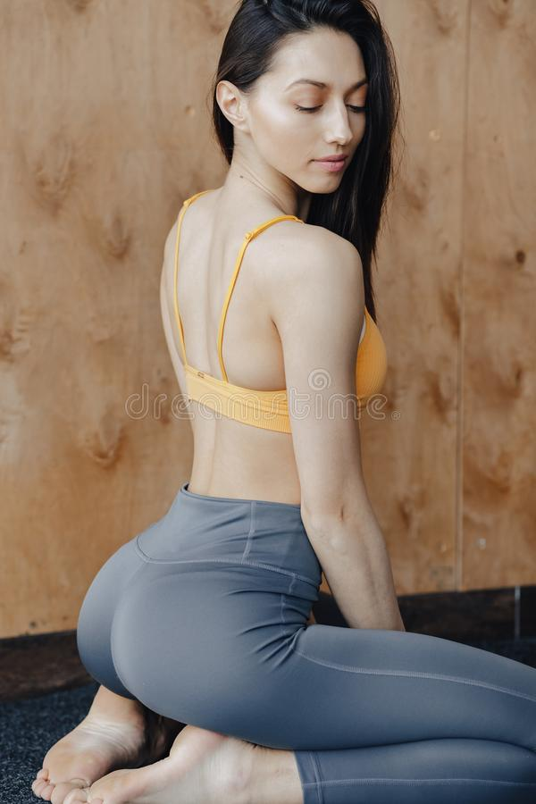 Молодая привлекательная девушка фитнеса сидя на поле около окна на предпосылке деревянной стены, отдыхая на занятиях йогой стоковые фото