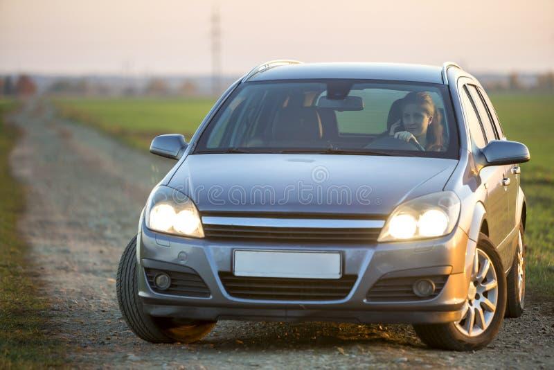 Молодая привлекательная длинн-с волосами усмехаясь женщина внутри сияющего серебряного автомобиля на руле говоря на мобильном тел стоковое изображение rf