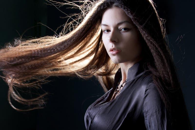 Молодая привлекательная женщина брюнета в темноте Красивое молодое изображение ведьмы на хеллоуин стоковое фото