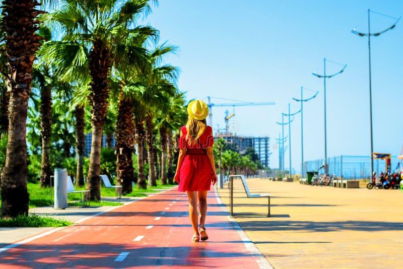 Молодая привлекательная женщина в красных прогулках платья вдоль пешеходной дороги с пальмами летом, около побережья Чёрного моря стоковые изображения