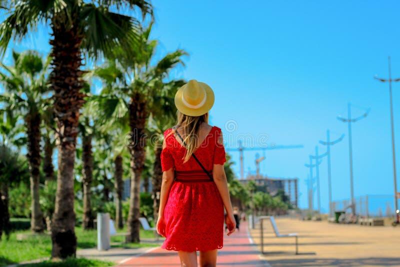 Молодая привлекательная женщина в красных прогулках платья вдоль пешеходной дороги с пальмами летом, около побережья Чёрного моря стоковое фото