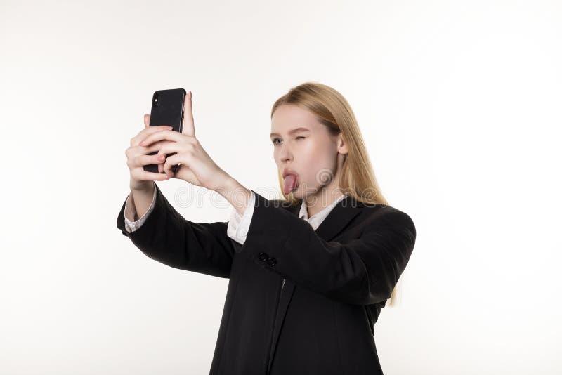 Молодая привлекательная женщина в темном костюме принимает фото используя мобильный телефон, закрывает один глаз и язык показыват стоковое изображение rf