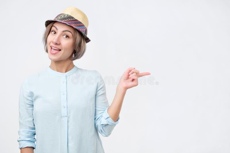 Молодая привлекательная женщина в шляпе лета и голубой рубашке указывая с ее пальцем на copyspace стоковое фото