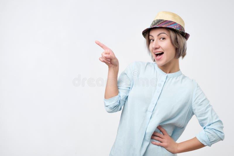Молодая привлекательная женщина в шляпе лета и голубой рубашке указывая с ее пальцем на copyspace стоковая фотография rf