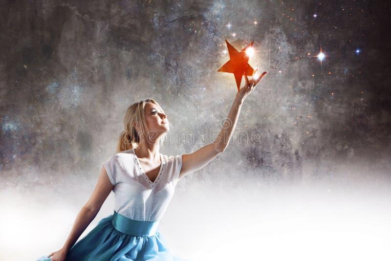 Молодая привлекательная женщина достигая для звезды Примите звезду от неба, мечт и планов, концепции стоковое изображение rf