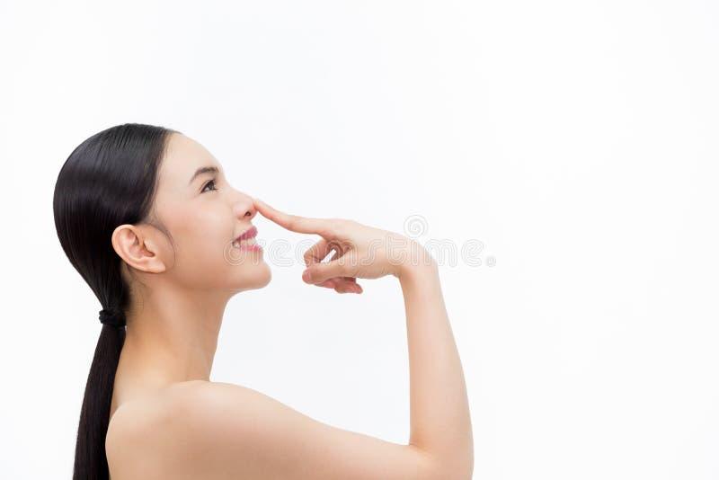Молодая привлекательная женщина касаясь ее носу с кончиком пальца над изолированной белой предпосылкой стоковое фото rf