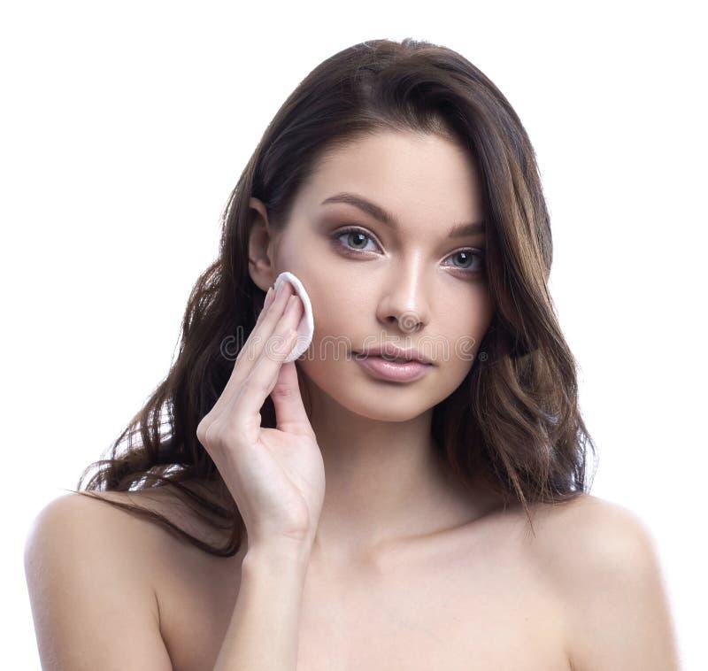 Молодая привлекательная женщина очищает сторону с пусковой площадкой хлопка Принципиальная схема Skincare стоковая фотография rf