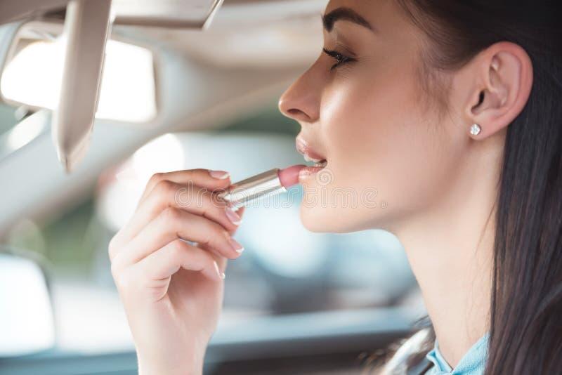 Молодая привлекательная женщина прикладывая губную помаду в автомобиле, используя солнце стоковая фотография rf