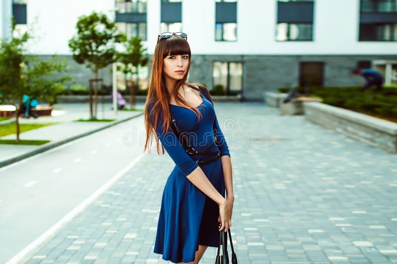 Молодая привлекательная женщина с длинными ногами с длинными волосами в голубом элегантном платье с поясом шпаги стоковые фотографии rf