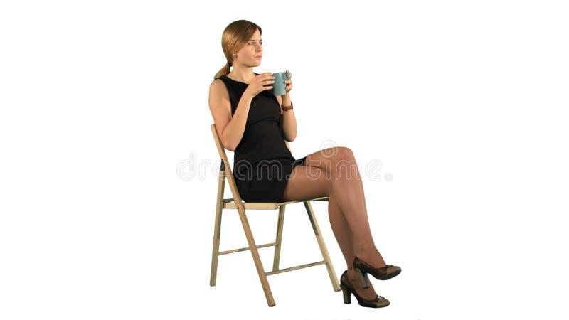 Молодая привлекательная женщина с чашкой кофе или чай на компьтер-книжке на белой изолированной предпосылке стоковое фото