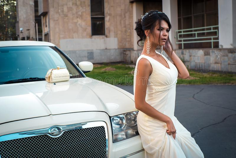 Молодая привлекательная женщина VIP в стойке платья около белого лимузина стоковое фото rf