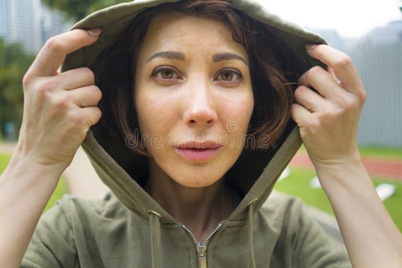 Молодая привлекательная и активная женщина jogger в верхней части hoodie готовой для разминки утра идущей на красивом парке город стоковые изображения