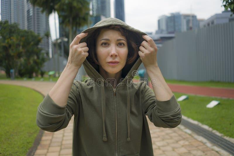 Молодая привлекательная и активная женщина jogger в верхней части hoodie готовой для разминки утра идущей на красивом парке город стоковое фото