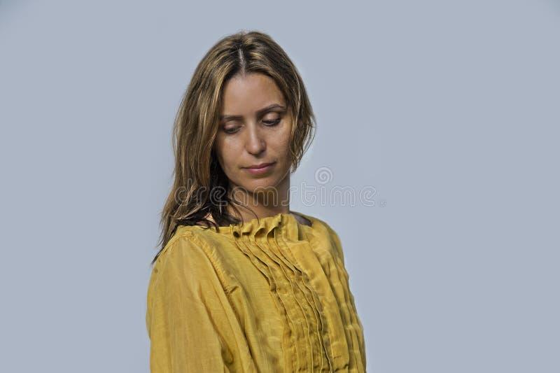 Молодая привлекательная и красивая профессиональная модельная женщина представляя нося сладкое желтое платье в красоте и идее про стоковые изображения rf