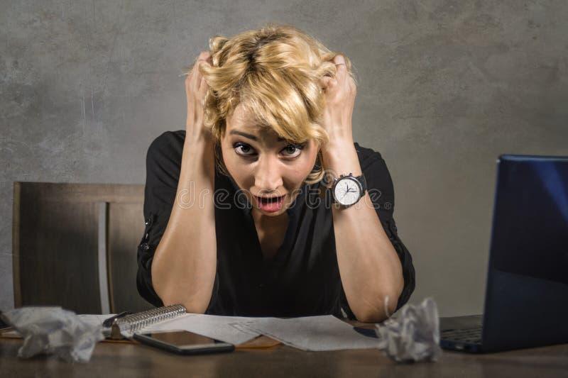 Молодая привлекательная и отчаянная бизнес-леди работая при портативный компьютер сидя на больном стола офиса кричащем и сокрушан стоковое фото