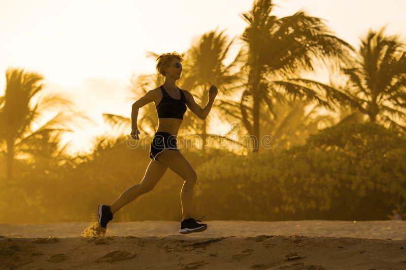 Молодая привлекательная и подходящая женщина бегуна при атлетическое тело бежать на разминке красивой тренировки света захода сол стоковые фотографии rf