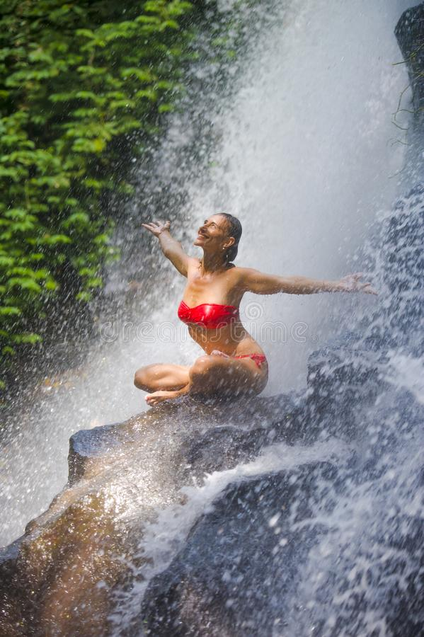 Молодая привлекательная и счастливая женщина при тело пригонки практикуя потока водопада рая йоги excited влажного нижнего тропич стоковые изображения rf