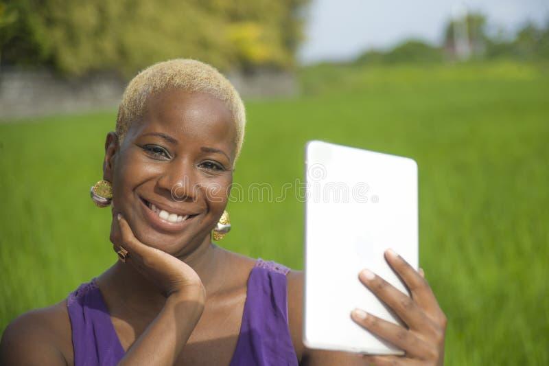 Молодая привлекательная и счастливая успешная черная афро американская женщина работая с цифровой пусковой площадкой таблетки out стоковое фото rf