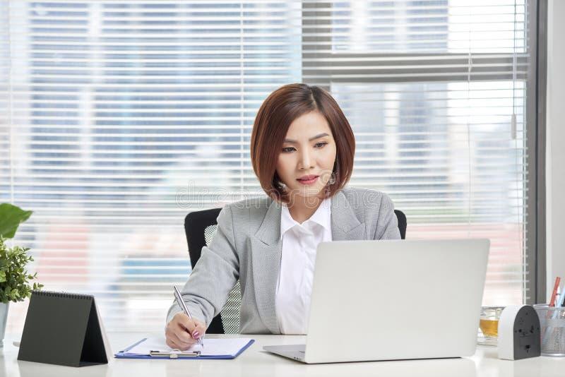 Молодая, привлекательная и уверенная бизнес-леди работая в офисе стоковое изображение