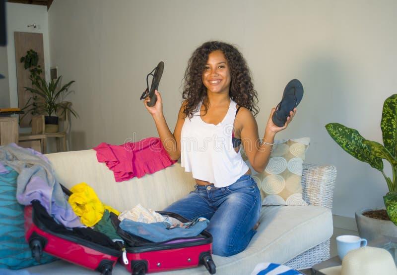 Молодая привлекательная и шальная счастливая латино-американская женщина подготавливая одежды пакуя вещество в чемодане выходя на стоковое изображение