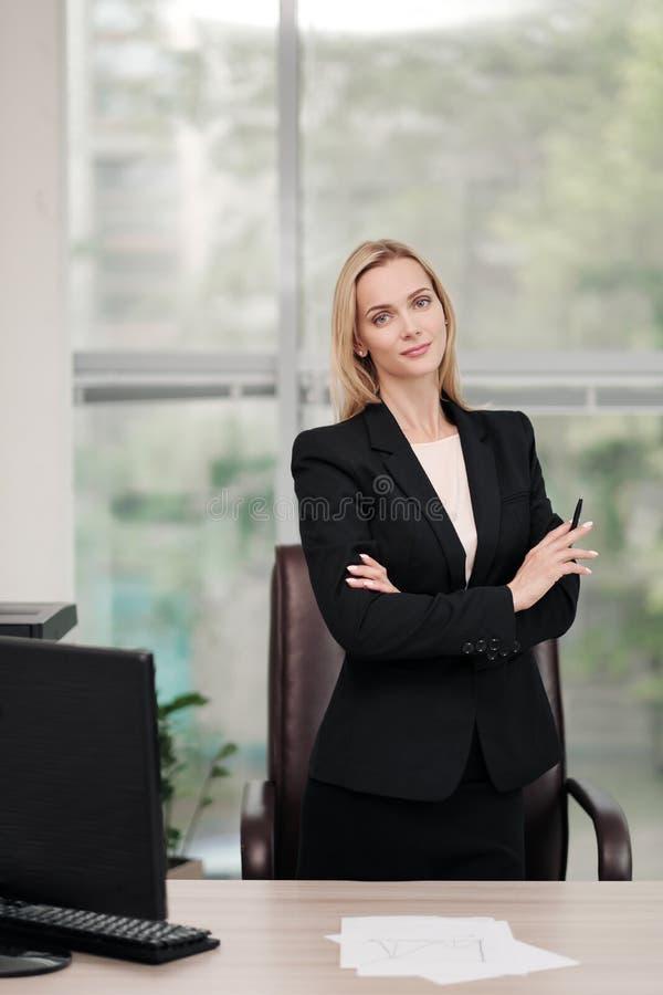 Молодая привлекательная кавказская белокурая женщина в черном деловом костюме сидит на столе в ярком офисе Изучать печатные докум стоковое изображение