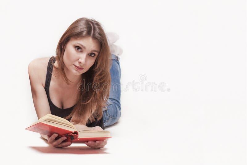 Молодая привлекательная кавказская женщина кладет на ноги пола вверх, книга с красной предусматрива в руках, немножко улыбкой Каш стоковые изображения