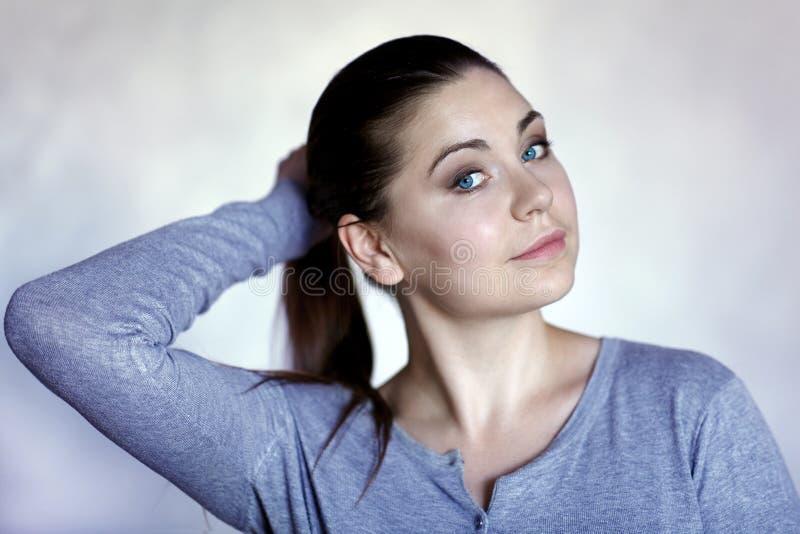 Молодая привлекательная кавказская женщина с голубыми глазами и темными волосами держит свой хвост в пони Улыбка, одетая в случай стоковое фото