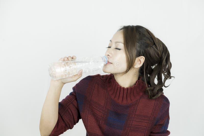 Молодая привлекательная красивая азиатская питьевая вода женщины от пластичной бутылки стоковые изображения rf