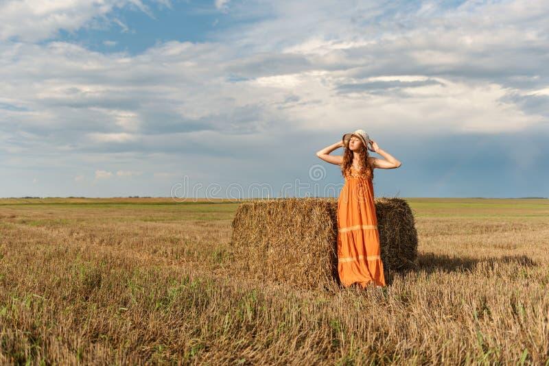 Молодая привлекательная курчавая сельская женщина в ретро винтажном платье и шляпе протягивая стойки около стога сжатой соломы пш стоковое изображение rf